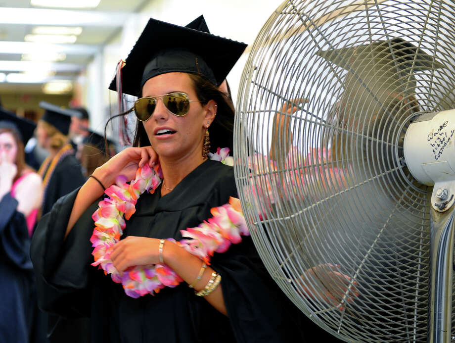 Graduate Molly Rose Robb cools herself in front of a big fan in the hallway before heading outside for Fairfield Warde High School's 8th Annual Commencement Exercises in Fairfield, Conn. on Thuursday June 21, 2012. Photo: Christian Abraham / Connecticut Post