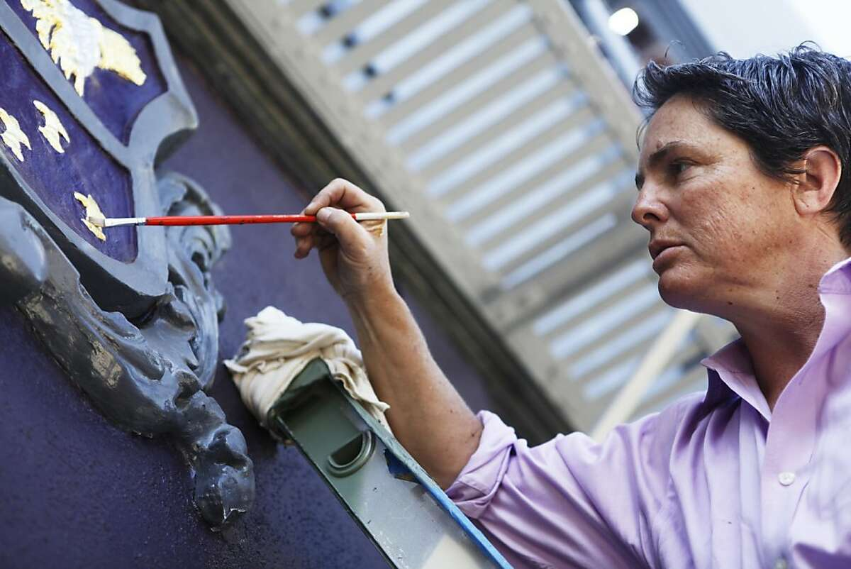 Nita Riccardi, owner of Winning Colors Painting, gilds decorative pieces on a building on 24th street in San Francisco, Calif. on Wednesday, June 20, 2012.