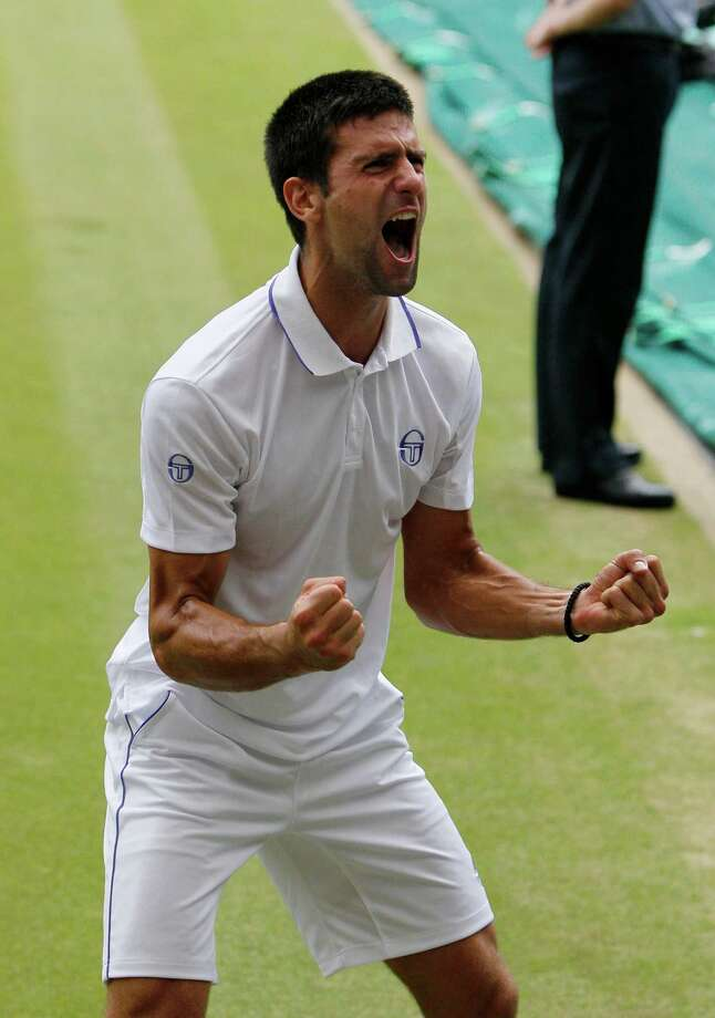 Serbia's Novak Djokovic celebrates after defeating Spain's Rafael Nadal in the men's singles final at the All England Lawn Tennis Championships at Wimbledon, Sunday, July 3, 2011. (AP Photo/Alastair Grant) Photo: Alastair Grant / AP