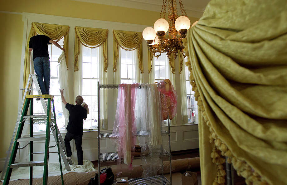 Patrick Roberts, left, and Scott Wengert hang drapes in  the yellow room called the Conservatory at the Texas Governor's Mansion on Wednesday, June 20, 2012, in Austin, Texas.  Four years ago the building was nearly destroyed in a fire started by an unknown arsonist. Gov. Rick Perry's office said Wednesday that pieces of the mansion's historic furniture collection are being moved back into the building. Perry and his family are expected to return in late July. Photo: Ralph Barrera, Associated Press / Austin American-Statesman