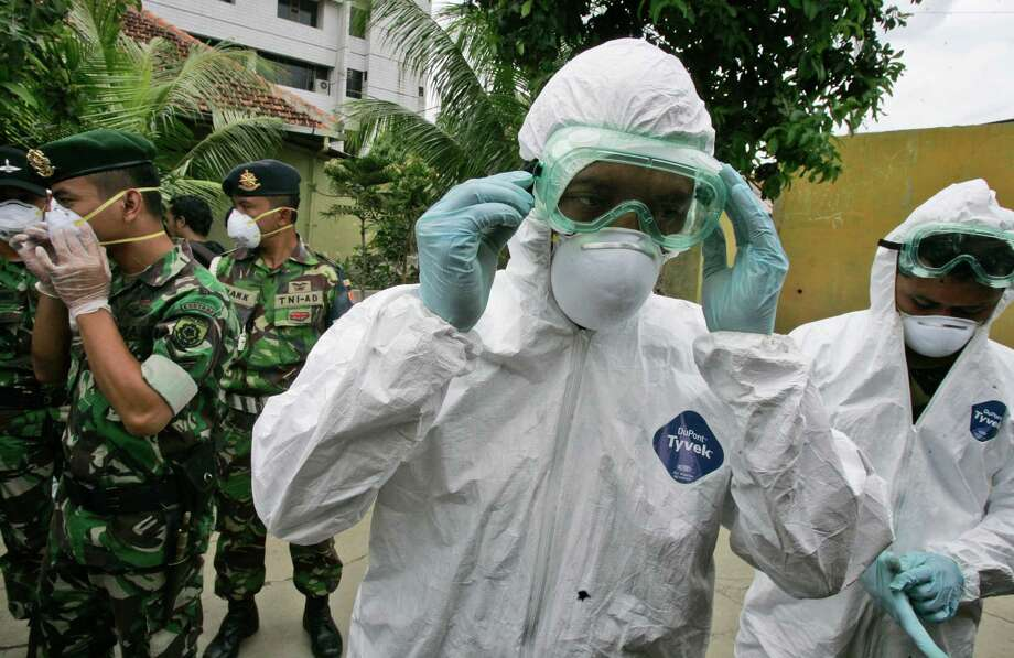 FILE - In this Tuesday, Dec. 16, 2008 file photo, soldiers wear protective gear during a bird flu prevention drill in Jakarta, Indonesia. The second of two bird flu studies once considered too risky to publish was released Thursday, June 21, 2012 ending a saga that pitted concerns about terrorism against fears of a deadly global epidemic. Both papers describe how researchers created virus strains that could potentially be transmitted through the air from person to person. Scientists said the results could help them spot dangerous virus strains in nature. (AP Photo/Irwin Fedriansyah) Photo: Irwin Fedriansyah