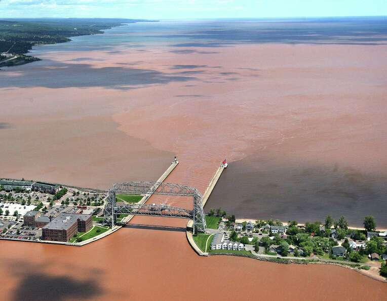 Clay-laden waters from the Duluth-Superior Harbor Basin pour out past the Aerial Left Bridge, throug