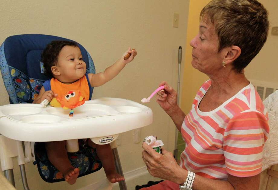 Patricia Hansen feeds her 11-month-old grandson, Jonathan Chabot, at home after she and her husband, Michael Hansen, were granted a permanent managing conservatorship of Jonathan in the 315th Juvenile District Court, Wednesday, June 20, 2012, in Houston. Jonathan, who tested positive for drugs when he was born, has lived with his grandparents since he was released from the hospital.  The Hansen's gave up their retirement dreams of living in Belize to come back to care for Jonathan. Photo: Melissa Phillip, Houston Chronicle / © 2012 Houston Chronicle