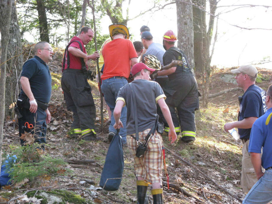 Photo by Gillian Scott Members of the West Glens Falls Fire department carry an injured mountain biker at Moreau Lake State Park several years ago. Local volunteer fire departments often shoulder the work of mountain rescues. Photo: Picasa