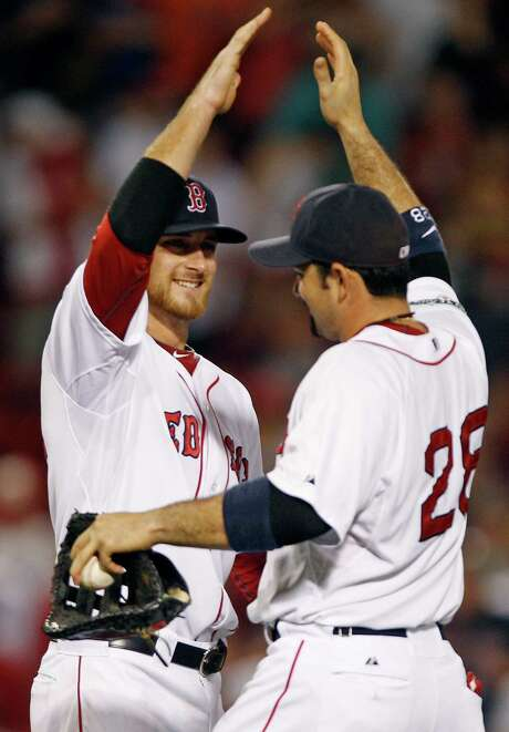 Boston Red Sox third baseman Will Middlebrooks, left, is congratulated by Adrian Gonzalez after their 6-5 win over the Miami Marlins in a baseball game at Fenway Park in Boston, Thursday, June 21, 2012. Photo: AP