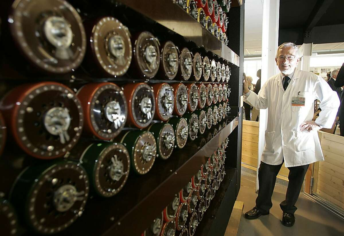 Mike Hillyard, one of the volunteers who rebuilt a replica of the Turing Bombe machine that played a crucial part in cracking the Nazi Enigma Code, stands by the machine at Bletchley Park in Milton Keynes, England, Tuesday, March 24, 2009. The original machine was destroyed after the war but volunteers rebuilt the replica that received a special Engineering Heritage Award on Tuesday to mark its place in history. (AP Photo/Akira Suemori)