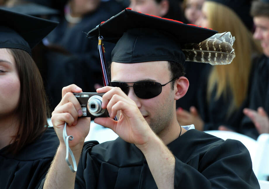 Graduate Joseph Delgado snaps photos of classmates, during Fairfield Warde High School's 8th Annual Commencement Exercises in Fairfield, Conn. on Thursday June 21, 2012. Photo: Christian Abraham / Connecticut Post
