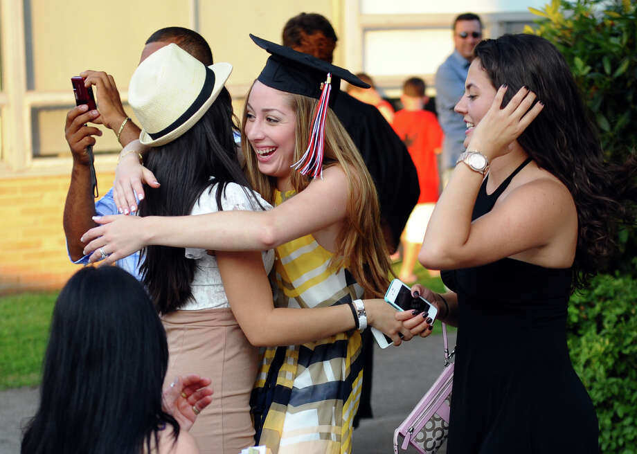 Graduate Morgana Ramos hugs her friend Leticia Parreira after Fairfield Warde High School's 8th Annual Commencement Exercises in Fairfield, Conn. on Thursday June 21, 2012. At right is friend Karoline Sales. Photo: Christian Abraham / Connecticut Post