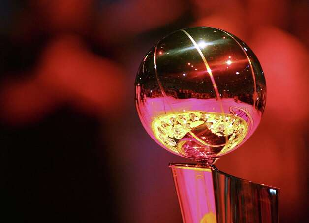 The Miami Heat championship rings are reflected in the Larry O'Brien NBA championship trophy before their NBA season opener against the Chicago Bulls in Miami, Florida, October 31, 2006.  REUTERS/Marc Serota   (UNITED STATES) Photo: MARC SEROTA, REUTERS / X00674