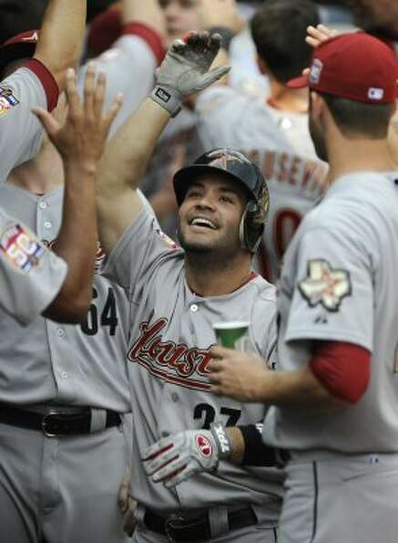 Jose Altuve, center, celebrates with teammates in the dugout after hitting a two-run home run. (Paul