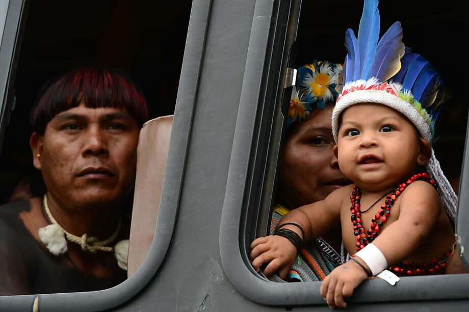 """Brazilian natives watch out from the bus upon arrival at RioCentro to hand out the Kari-Oca II Declaration to leaders attending the UN Conference on Sustainable Development, Rio+20, in Rio de Janeiro, Brazil, on June 21, 2012. World leaders attending the UN summit in Rio weighed steps to root out poverty and protect the environment as thousands of activists held several protests to denounce Amazon rainforest deforestation, the plight of indigenous peoples and the """"green economy"""" being advocated at the UN gathering.  AFP PHOTO / CHRISTOPHE SIMONCHRISTOPHE SIMON/AFP/GettyImages Photo: Christophe Simon, AFP/Getty Images"""