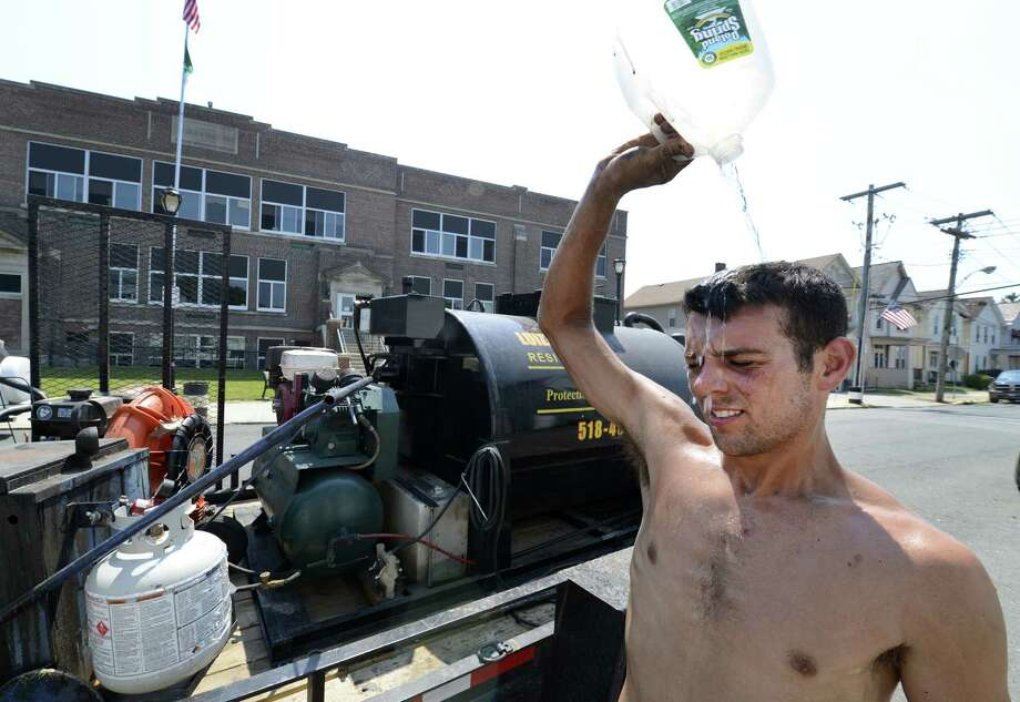 Ryan Babin of the Luizzi Sealcoating throws some water over his head to cool down after putting down driveway sealant in Green Island, N.Y. June 22, 2012.(Skip Dickstein/Times Union). Photo: Skip Dickstein / 00018199A