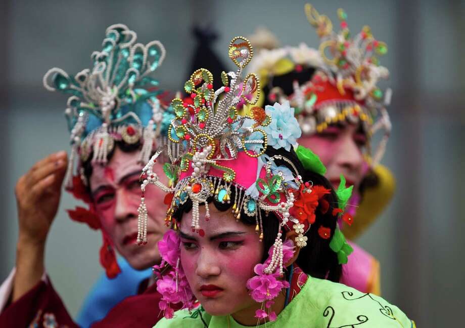 Chinese dancers dressed in traditional costumes wait for their performance ahead of the opening ceremony of Duanwu Festival held at Shunyi Olympic Rowing-Canoeing Park in Beijing, China Friday, June 22, 2012. The Duanwu festival, also known as Dragon Boat festival, which falls on the fifth day of the fifth month of the Chinese calendar, commemorates the death of Qu Yuan, a famous Chinese poet from the kingdom of Chu who lived during the Warring States period. (AP Photo/Andy Wong) Photo: Andy Wong, Associated Press / AP