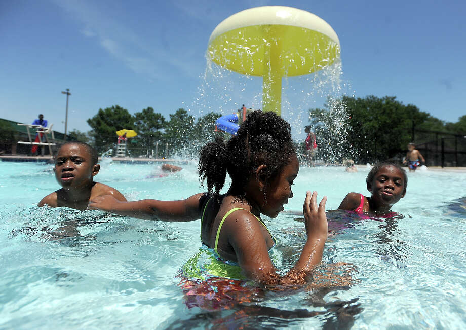 Children wade in the shallow end of the pool during opening day at Magnolia Park pool in Beaumont, Saturday, June 2, 2012. Tammy McKinley/The Enterprise Photo: TAMMY MCKINLEY