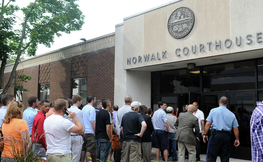A long line forms outside the Norwalk Court house on Belden Street in Norwalk, Conn. after a power outage left the building without lights, air conditioning, computers or metal detectors on Friday, June 22, 2012. Those with business at the courthouse filed through the lobby where a table was set up with paper files and all cases were grated continuances. Photo: Lindsay Niegelberg / Stamford Advocate