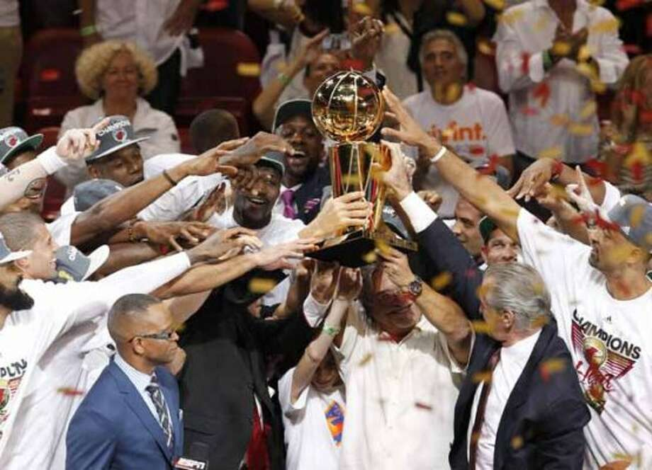 The Miami Heat celebrate with the the Larry O'Brien NBA Championship Trophy after Game 5 of the NBA finals basketball series against the Oklahoma City Thunder, Thursday, June 21, 2012, in Miami. The Heat won 121-106 to become the 2012 NBA Champions. (AP Photo/Wilfredo Lee) (AP)