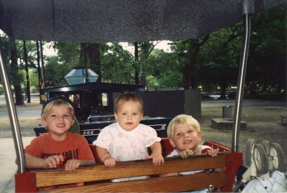 "Siblings Clinton, 5, Emily, 1, and Brett Bippert, 3, ride the Breckenridge Park Train in 1994. From their mother, Frances Bippert: ""These photos were taken during my children's favorite adventure, the train ride, after our visit to the zoo. It was the best way to cool off after the long, hot tour of the zoo."" Photo: COURTESY"