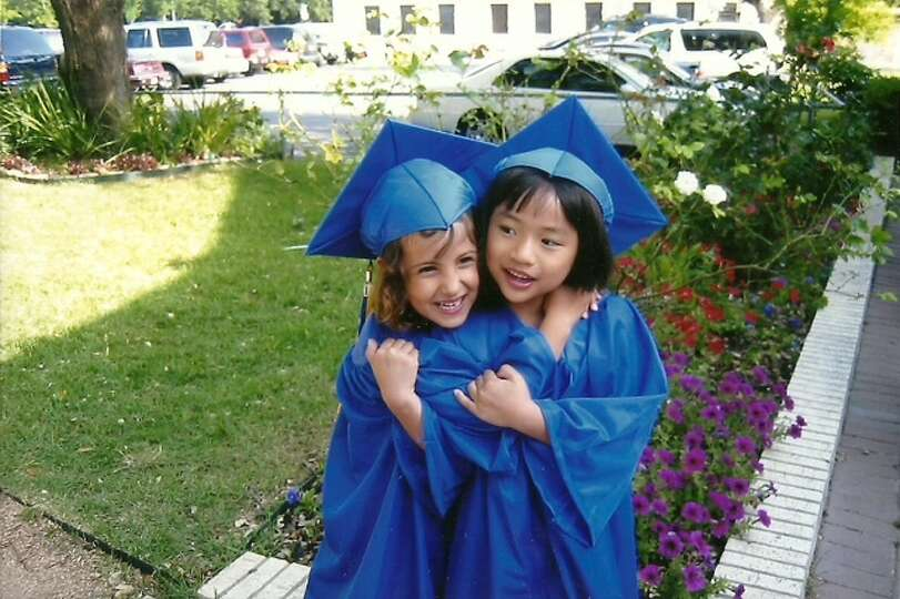 Annie Acquart and Bella Salazar celebrate their kindergarten graduation from St. Anthony Catholic Sc