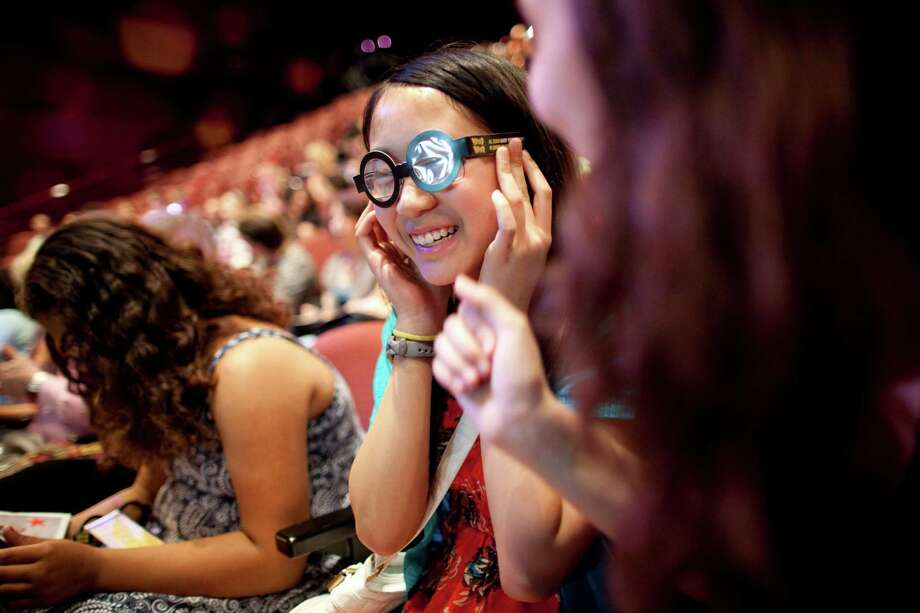 """Jennifer Loo, 13, tries on Harry Potter-style frames while sitting with other students at the """"Potted Potter"""" show at the Little Shubert Theatre in New York. The performance is a 70-minute mad dash through all the Harry Potter books retold by Daniel Clarkson and Jefferson Turner. Photo: BRIAN HARKIN / NYTNS"""