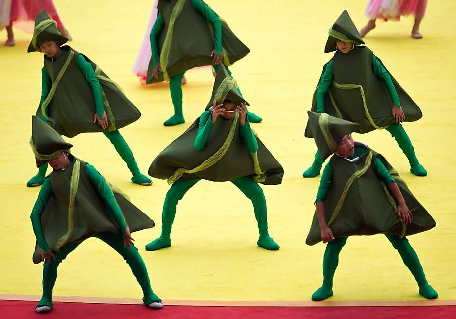 A Chinese child, center, adjusts his rice dumpling shaped hat while performing on a stage during the opening of the Duanwu Festival held at Shunyi Olympic Rowing-Canoeing Park in Beijing, China Friday, June 22, 2012. Rice dumplings are traditionally eaten during the Duanwu festival, also known as the Dragon Boat festival, which falls on the fifth day of the fifth month of the Chinese calendar, commemorating the death of Qu Yuan, a famous Chinese poet from the kingdom of Chu who lived during the Warring States period. (AP Photo/Andy Wong) Photo: Andy Wong, Associated Press