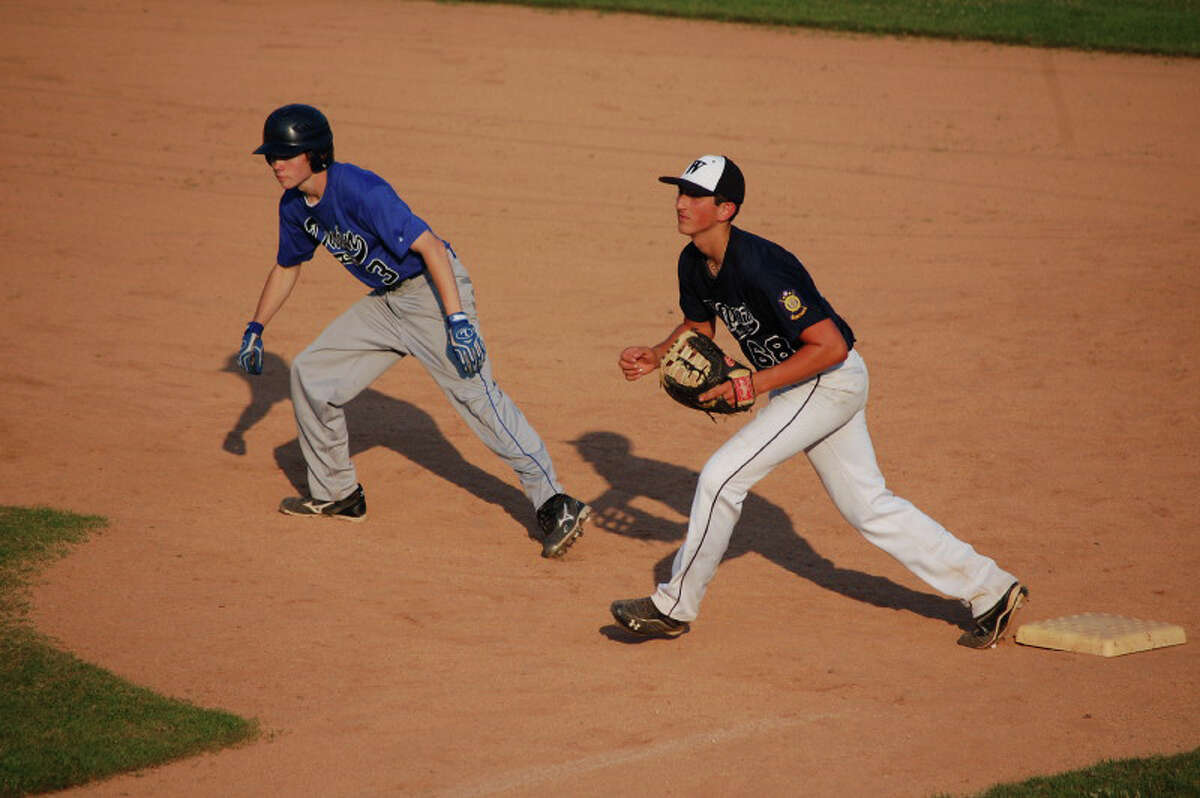 Westport first baseman Frank Vartuli tries to keep Darien base runner Carl Stowell at bay Thursday in Westport's 2-1 win.