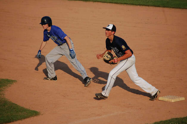 Westport first baseman Frank Vartuli tries to keep Darien base runner Carl Stowell at bay Thursday in Westport's 2-1 win. Photo: Robert Chasin / Contributed Phot