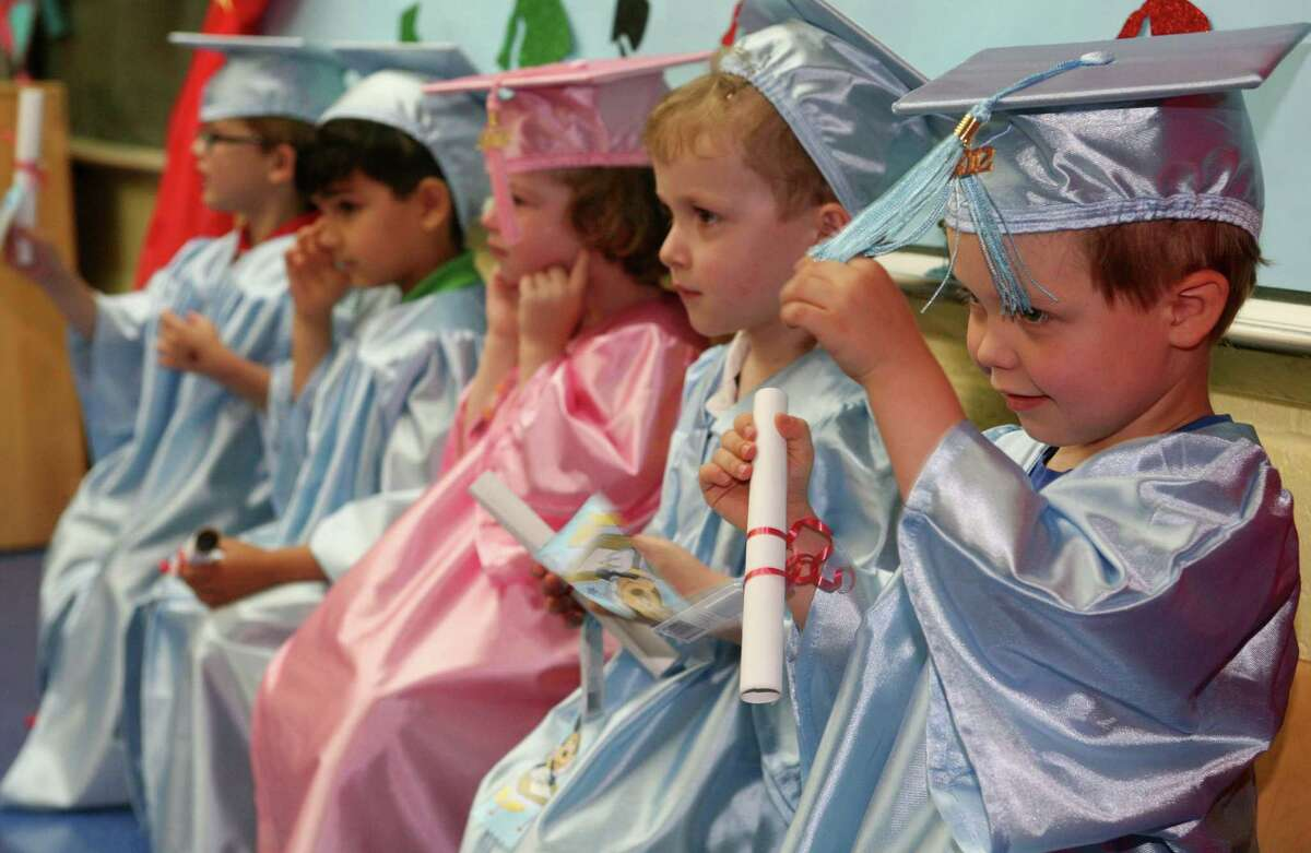 Pat-a-Cake Playschool graduate Joey Hamlen, 4, plays with his tassle during the school's