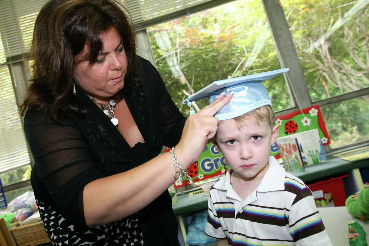 """Pat-a-Cake graduate Charlie Glines, 4, gets help with his cap from his teacher Lisa Pudano before the start of the school's """"moving up ceremony"""" Friday June 22, 2012."""