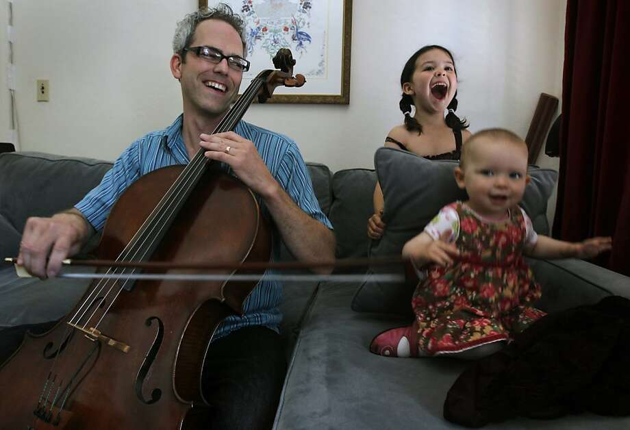 Musician Alex Kelly plays the cello for his daughters Dahlia, 6, and Clara, 16 months, at their home in San Francisco, Calif. on Wednesday, June 20, 2012. Photo: Paul Chinn, The Chronicle