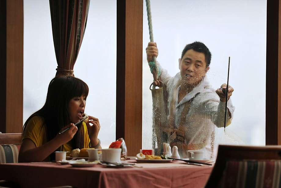 Mind if I join you? A window washer intrudes upon breakfast on the 23rd floor of a hotel in Ningbo, China. Photo: Peter Parks, AFP/Getty Images