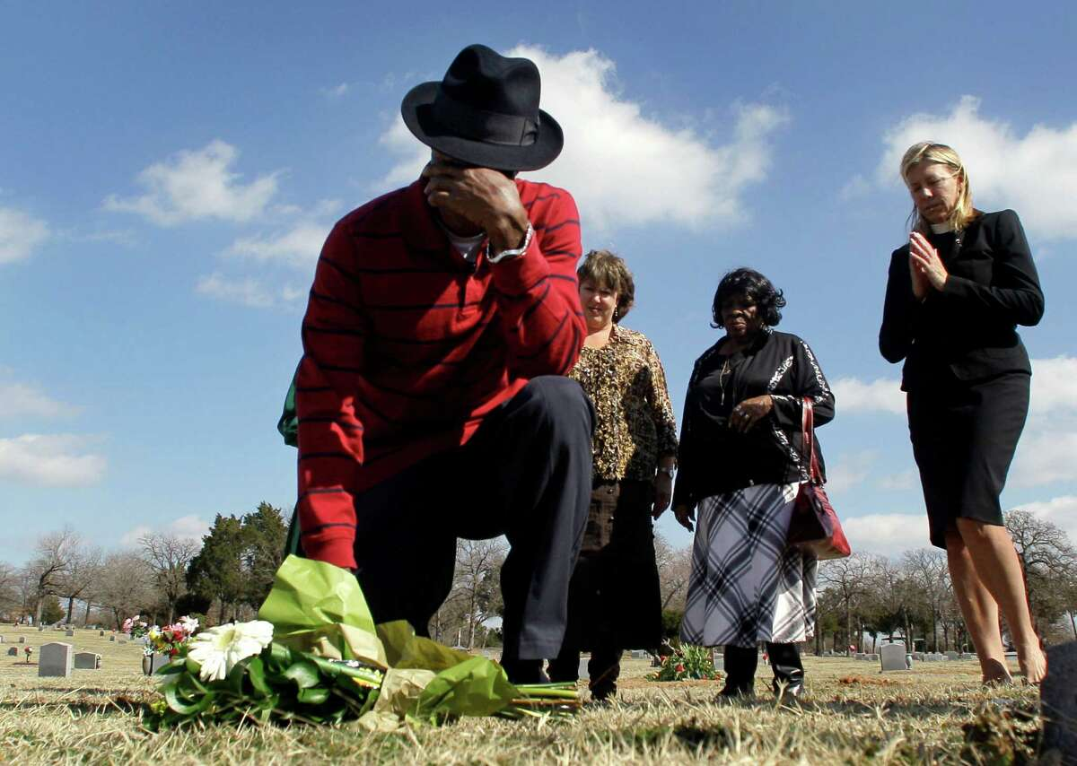 File - In this Feb. 15, 2011 file photo, File - In this Feb. 15, 2011 file photo, Larry Sims, front, kneels and prays as he places flowers at his mother's unmarked grave as Michelle Moore, from left rear, Dearline Sims and The Rev. Dorothy Budd, right rear, look on in Dallas. DNA testing helped free Sims from a Texas prison after serving 24 years for sexual assault, but the district attorney never declared him formally innocent, barring him from receiving any compensation from the state. Sims died in June 2012, and friends and other ex-inmates say he struggled after prison with finding work and happiness.