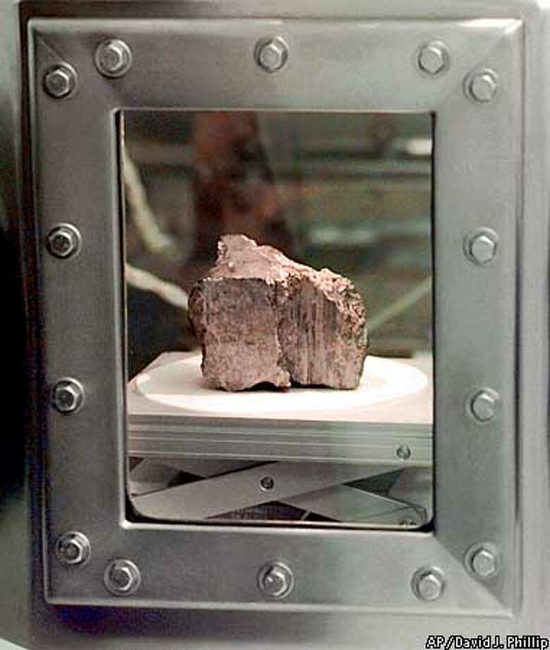 The meteorite labeled ALH84001 sits in a chamber at a Johnson Space Center lab in Houston, Wednesday, Aug. 7, 1996. Researchers at NASA and three universities claimed Wednesday to have found in the rock from Mars organic compounds that they say were deposited by primitive life forms before the rock was blasted into space and sent on a 15 million-year voyage to Earth. (AP Photo/David J. Phillip)