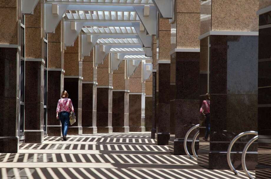 A visitor to the new North Las Vegas City Hall building walks down an outdoor corridor lined with marble columns, Thursday, June 21, 2012, in North Las Vegas, Nev. Despite its suburban trimmings, this blue-collar, family-oriented city outside Las Vegas is officially a disaster area. After five years of declining property taxes, massive layoffs and questionable spending choices, North Las Vegas city leaders declared a state of emergency earlier this month. (AP Photo/Julie Jacobson) Photo: Julie Jacobson
