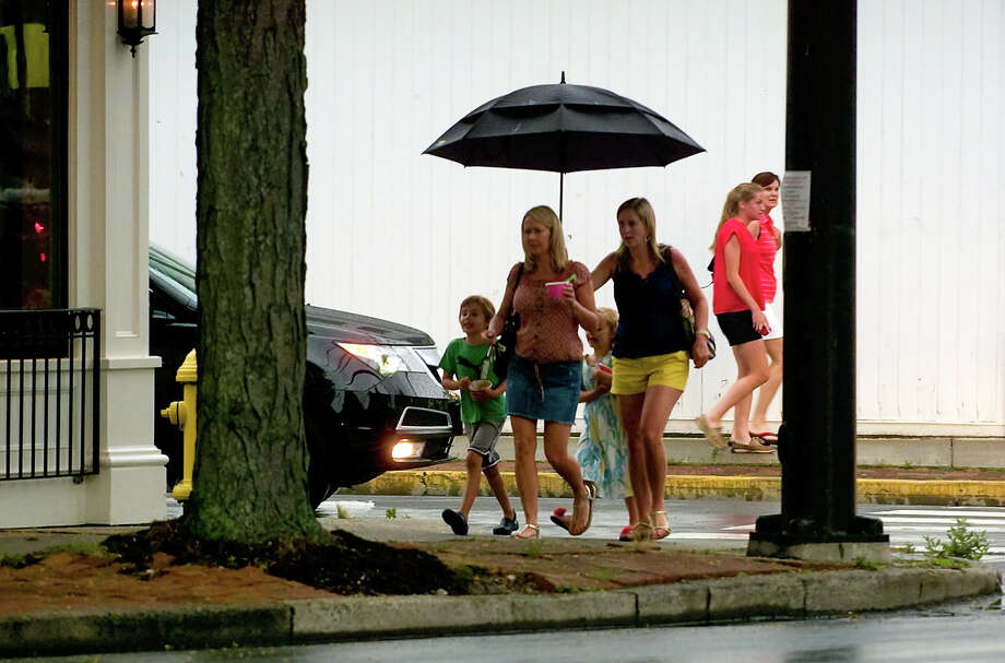 Jenna Adikes, of New York City, holds a big umbrella over her sister Kristen Lynch, of Fairfield, and her two children Jackson Lynch, 6, and Brooke Lynch, 5, while strolling along Post Road in downtown Fairfield, Conn. on Friday June 22, 2012. Photo: Christian Abraham / Connecticut Post