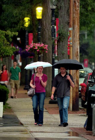 A couple makes their way in the rain along Post Road in downtown Fairfield, Conn. on Friday June 22, 2012. Photo: Christian Abraham / Connecticut Post