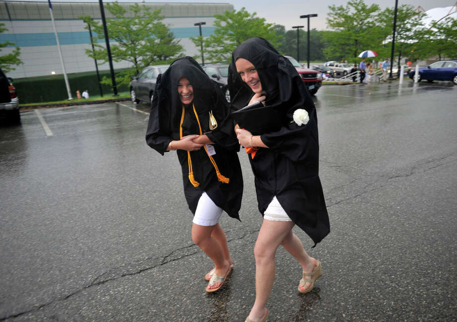 Hannah Cacciato, left, and Helen Fahey cover themselves from the rain with their gowns while leaving the O'Neill Center after the Ridgefield High School graduation at Western Connecticut State University's westside campus on Friday, June 22, 2012. Photo: Jason Rearick / The News-Times