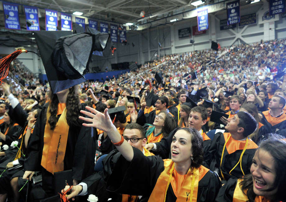 Becca Maher, center, and other graduates from the Class of 2012 toss their caps in the air during the Ridgefield High School graduation at the O'Neill Center at Western Connecticut State University's westside campus on Friday, June 22, 2012. Photo: Jason Rearick / The News-Times