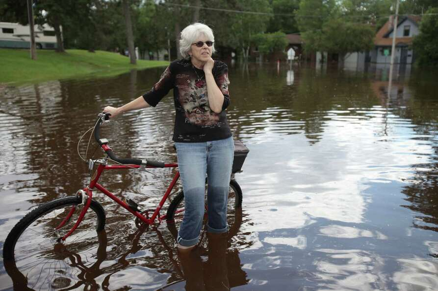 Jane Klejeski of Moose Lake pauses to take in the scene of the flooded streets near the Moose Lake H