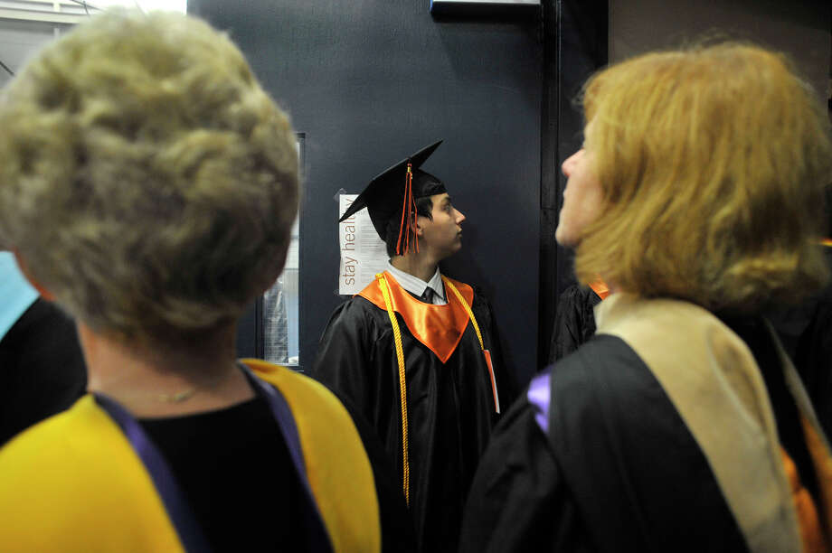 Alex Abrahams waits in line before the graduates process in during the Ridgefield High School graduation at the O'Neill Center at Western Connecticut State University's westside campus on Friday, June 22, 2012. Photo: Jason Rearick / The News-Times