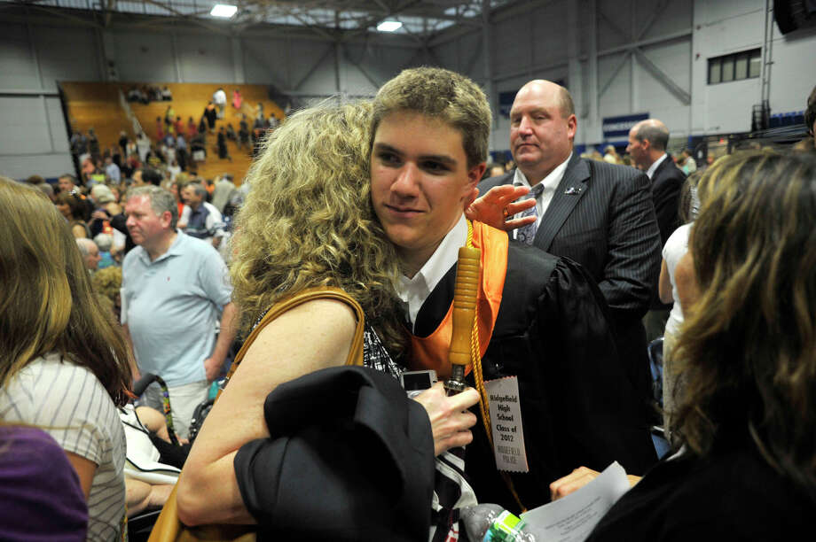 Brian Johnson, right, hugs his aunt Karen DePaoli following the Ridgefield High School graduation at the O'Neill Center at Western Connecticut State University's westside campus on Friday, June 22, 2012. Photo: Jason Rearick / The News-Times