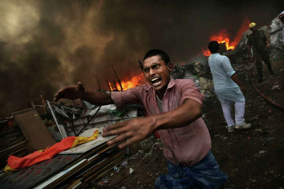 An Indian shouts for water as a shanty town is engulfed in flames in New Delhi, India, Friday, June 22, 2012. A fire swept through a slum in the Indian capital on Friday, destroying hundreds of shanties where residents had collected scrap plastic and rubber for resale. No one was reported injured or killed, fire department chief A.K. Sharma said. Photo: Kevin Frayer, Associated Press / AP