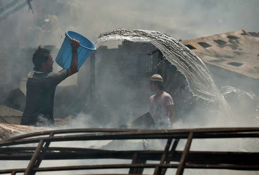 A resident helps extinguish a fire at a slum cluster in New Delhi on June 22, 2012.