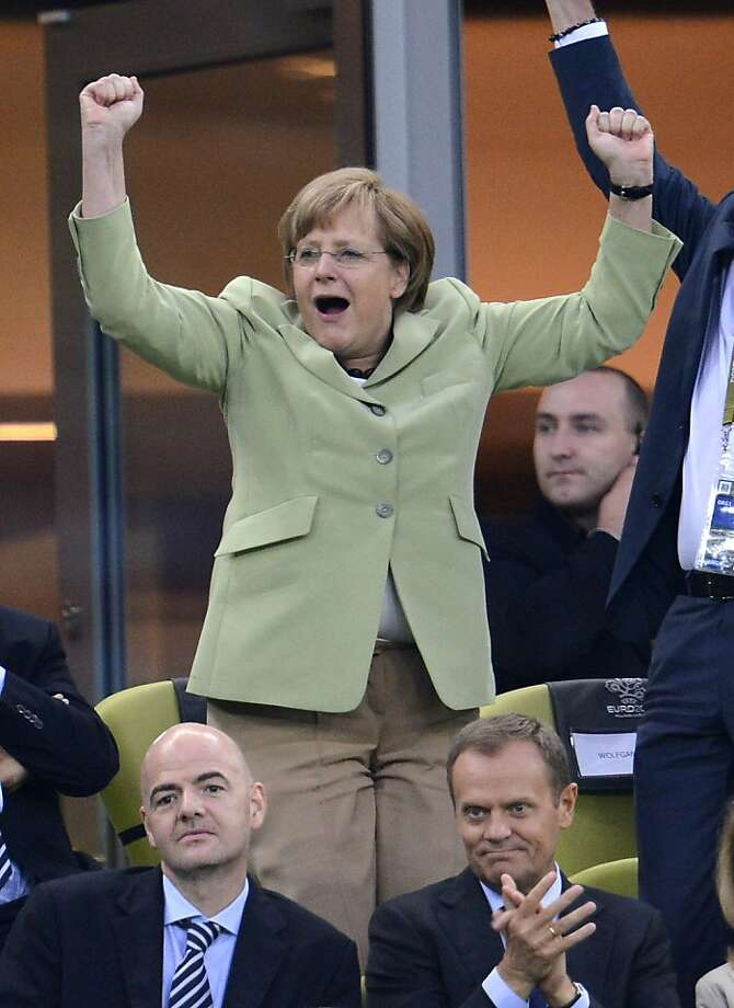 German Chancellor Angela Merkel (top) celebrates after Germany scored during the Euro 2012 football championships quarter-final match Germany vs Greece on June 22, 2012 at the Gdansk Arena.     AFP PHOTO / FABRICE COFFRINIFABRICE COFFRINI/AFP/GettyImages Photo: Fabrice Coffrini, AFP/Getty Images