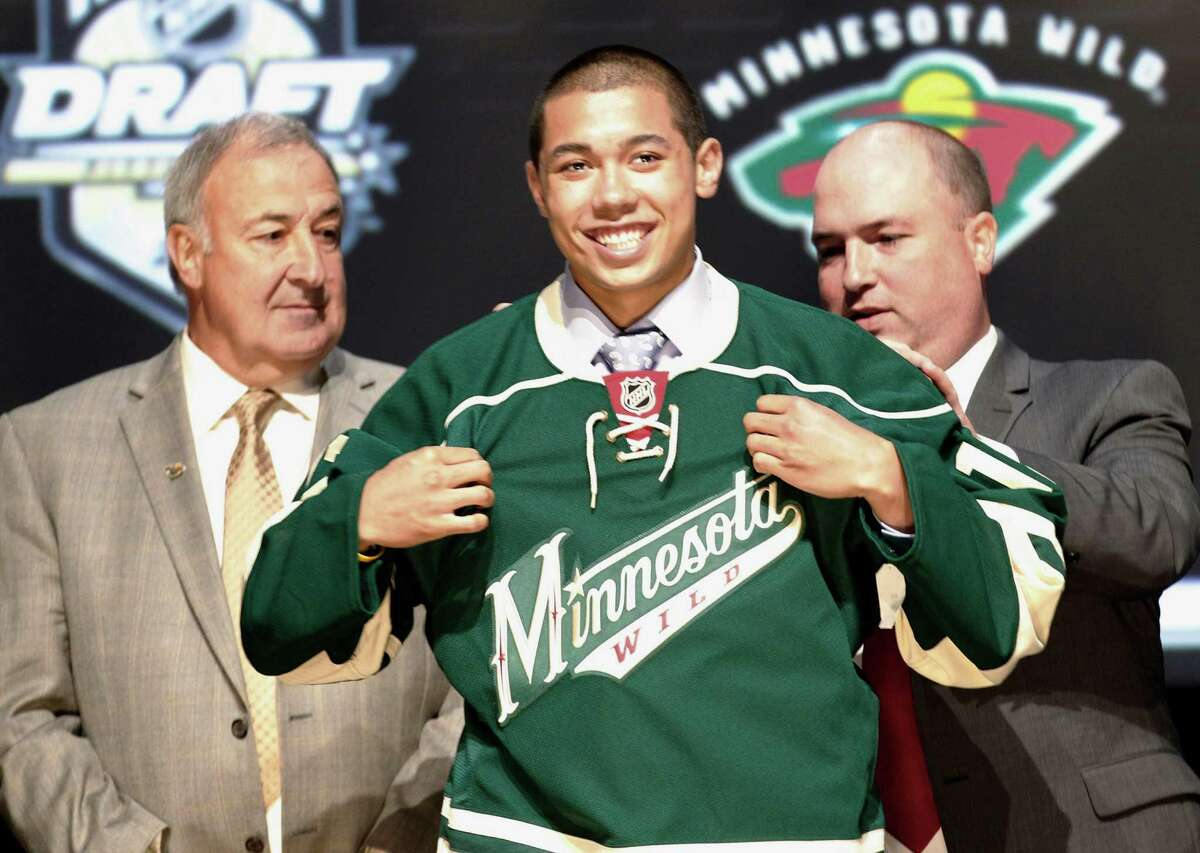 Matthew Dumba, center, a defenseman, smiles with officials from the Minnesota Wild after being chosen seventh overall in the first round of the NHL hockey draft on Friday, June 22, 2012, in Pittsburgh. (AP Photo/Keith Srakocic)