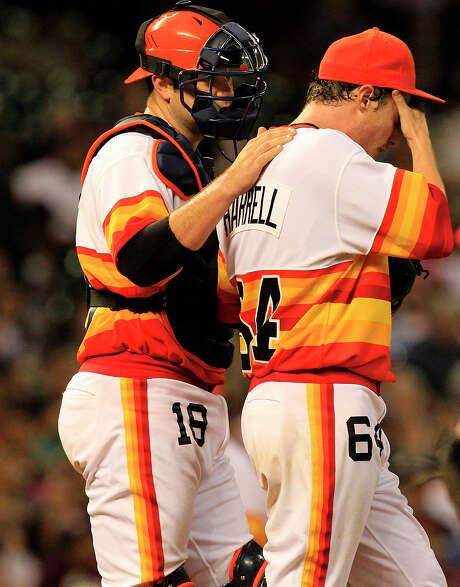 Lucas Harrell, right, needs consoling by catcher Chris Snyder. The Astros pitcher took the loss despite allowing two hits in seven innings. Photo: Cody Duty / © 2011 Houston Chronicle