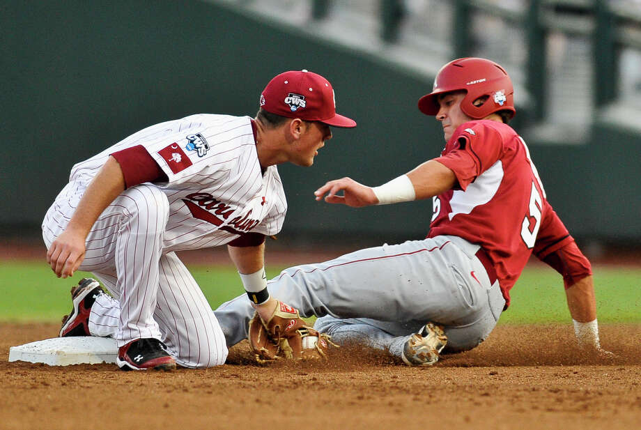Arkansas' Matt Reynolds, right, is safe after stealing second base against South Carolina shortstop Joey Pankake in the first inning of an NCAA College World Series baseball elimination game in Omaha, Neb., Friday, June 22, 2012. The winner advances to play Arizona in the championship series. (AP Photo/Eric Francis) Photo: Eric Francis