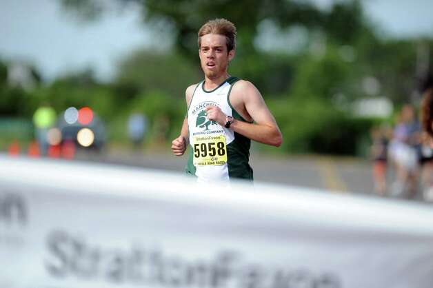 Jacob Gurzler, of Manchester, crosses the finish line in first place during the 32nd Stratton Faxon 5K Saturday, June 23, 2012 at Jennings Beach in Fairfield, Conn. Photo: Autumn Driscoll / Connecticut Post