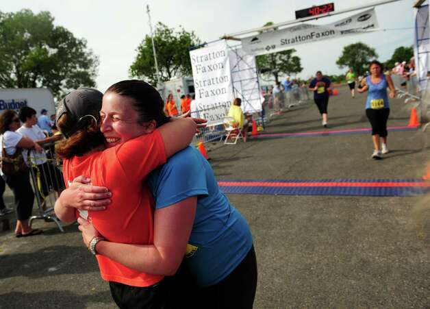 Tracy Minsky, of Fairfield, hugs friend Ginny Bentley after crossing the finish line during the 32nd Stratton Faxon 5K Saturday, June 23, 2012 at Jennings Beach in Fairfield, Conn.   It is Minsky's first-ever 5k.  She did it with help from friends and the âÄúCouch to 5KâÄù program, which she started in April. Photo: Autumn Driscoll / Connecticut Post