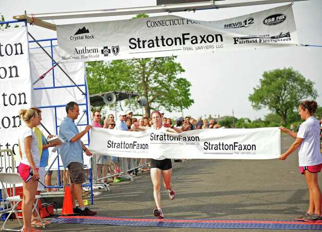 Sharon Lemberger, of Stamford, crosses the finish line during the 32nd Stratton Faxon 5K Saturday, June 23, 2012 at Jennings Beach in Fairfield, Conn.  Lemberger was the first female finisher. Photo: Autumn Driscoll / Connecticut Post