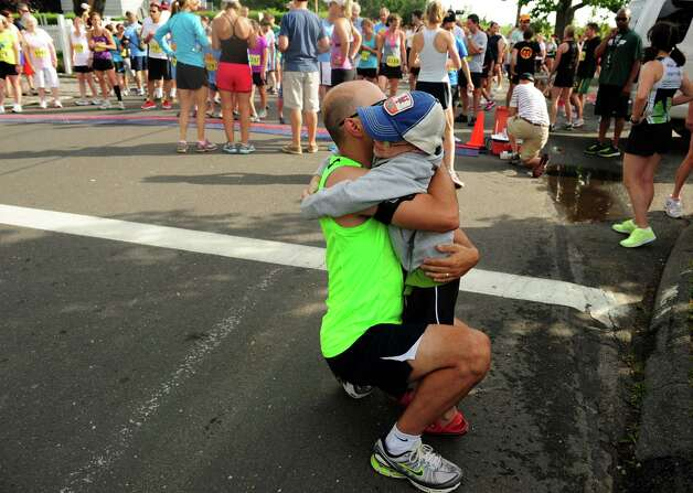 Six-year-old CJ Peterson gives his dad, Craig, a hug for good luck before the 32nd Stratton Faxon 5K Saturday, June 23, 2012 at Jennings Beach in Fairfield, Conn. Photo: Autumn Driscoll / Connecticut Post
